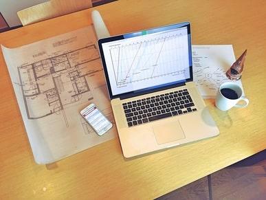 Tietokone ja suunnittelupiirrustus pöydällä