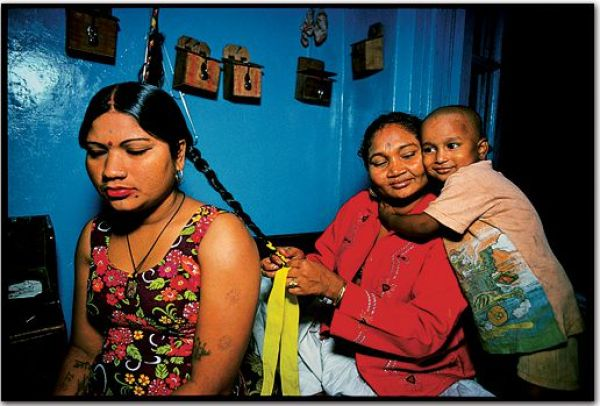 Η ιδιοκτήτρια του οίκου ανοχής ετοιμάζει την νεαρή ιερόδουλη ενώ ο γιος της κοπέλας δείχνει απόλυτα εξοικειωμένος με το περιβάλλον και την αγκαλιά της ιδιοκτήτριας
