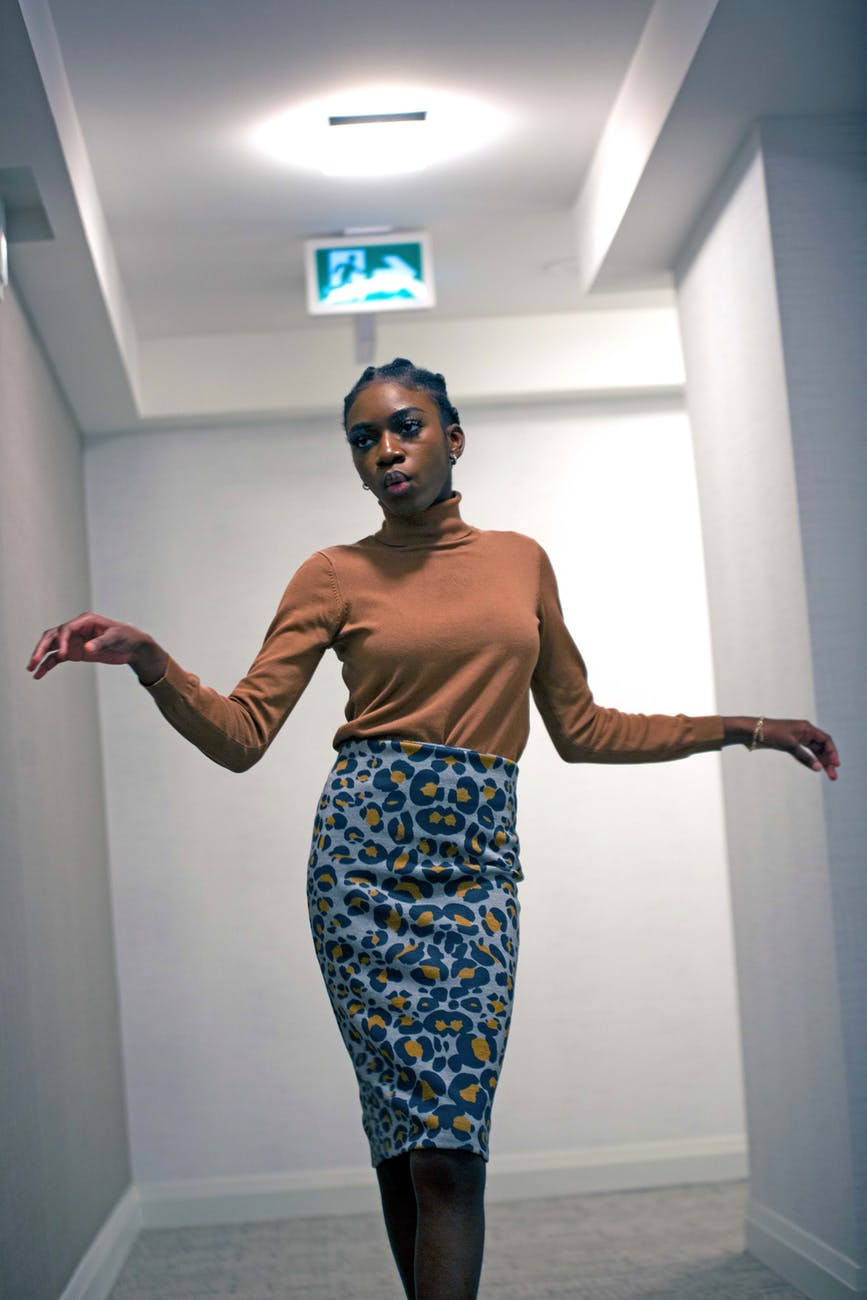 young black woman dancing in hallway of modern building