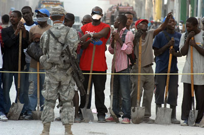 Haitians waiting for jobs shoveling rubble from the streets in Port-au-Prince enjoy pop music played by U.S. soldiers Feb. 25