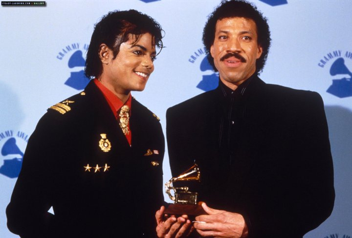 "On February 25, 1986, at the 28th Grammy Awards from Shrine Auditorium in Los Angeles, California, songwriters Michael Jackson and Lionel Richie are honored with the ""Best Song of the Year"" award for ""We Are The World"", the relief single they wrote for the ""USA For Africa"" project in 1985. The song is also voted as the ""Record of the Year "", an award accepted by producer Quincy Jones, joined on stage by Jackson, Lionel Richie, Stevie Wonder and Dionne Warwick; after the speech, Michael Jackson exits the stage happily and tightly holding mentour and friend Stevie Wonder's hand. The other honors for ""We Are The World"" are the ""Best Pop Performance By Duo or Group"" and ""Best Short Form Video""."