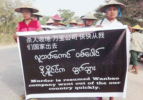 Anti-mine protesters hold a multilingual protest sign during a recent demonstration. Photo: Supplied