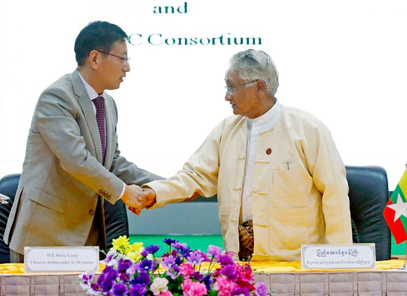 Commerce minister U Than Myint (right), shakes hands with Hong Liang (left), Chinese Ambassador to Myanmar, after the signing ceremony of the framework agreement on Kyaukphyu special economic zone in the capital. Photo - EPA