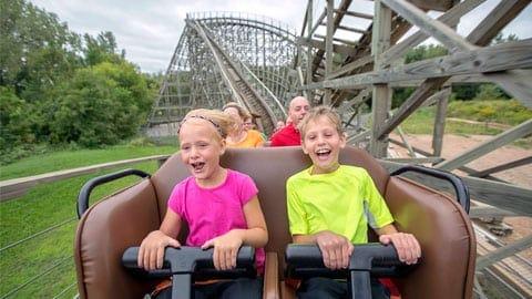 kids smiling on rollar coaster ride