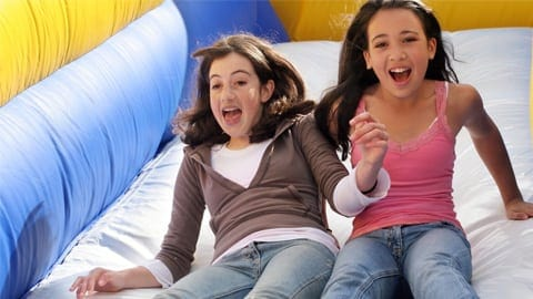 girls sliding down a bounce house at the big thrill factory