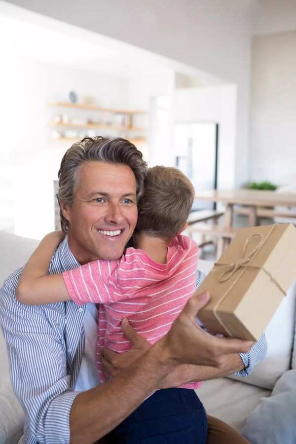 Father embracing son while receiving gift in living room
