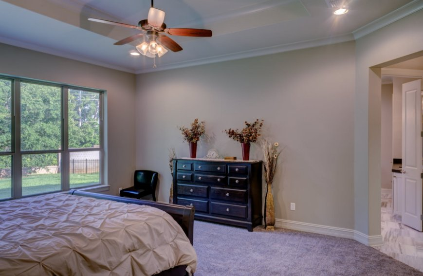 Brown ceiling fan with light bulbs in bedroom