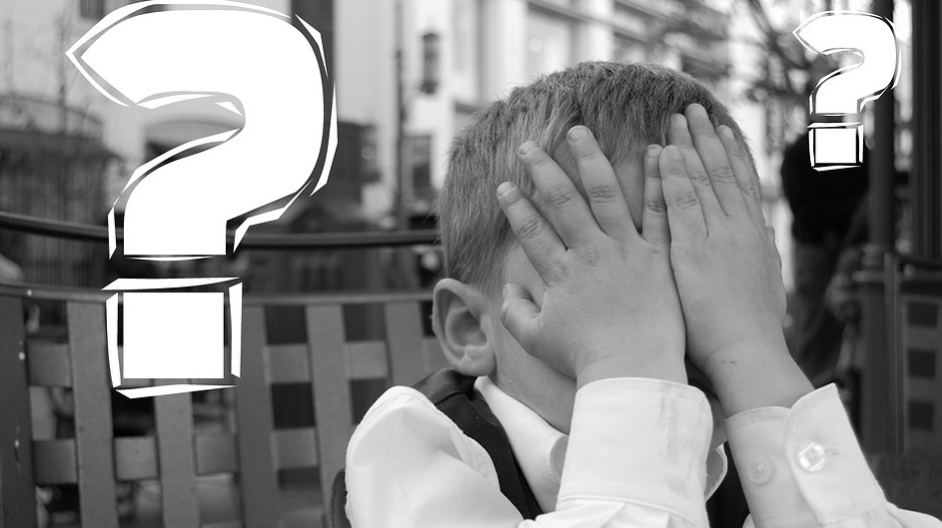 A boy covering his face with animated question marks around his head