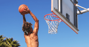 A young man shooting hoop with a basketball