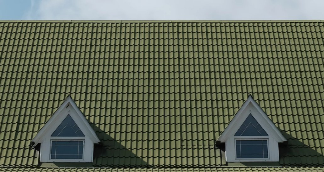 green shingled roof with two attic windows