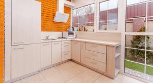 A remodeled kitchen with orange brick walls