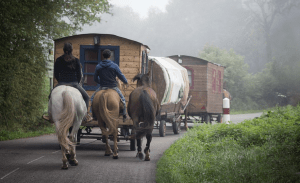 People riding horses and moving a caravan