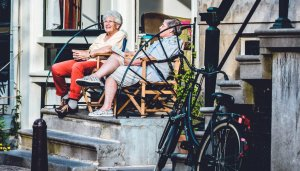 An older couple sitting on short cement outdoor steps
