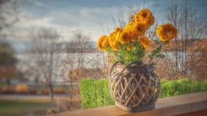 Orange and yellow mixed flowers in a wicker basket on a porch