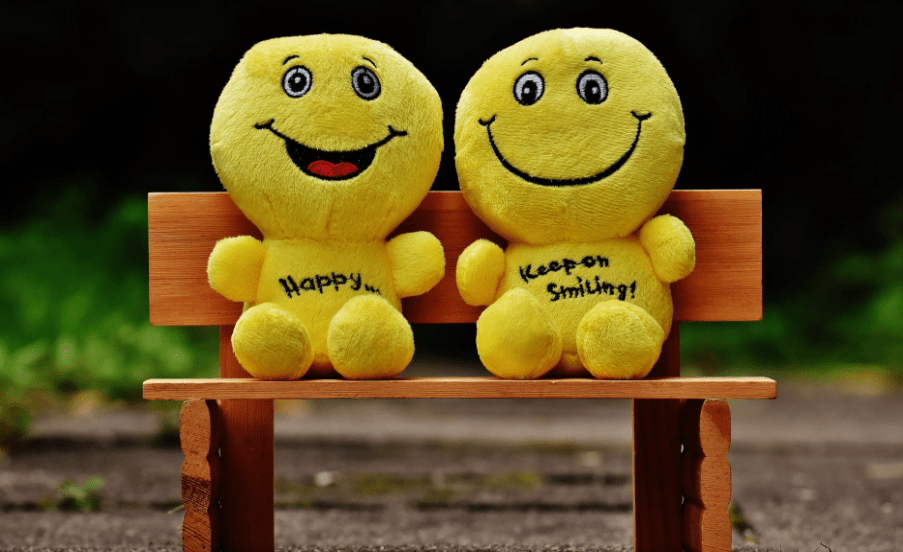 Two yellow smiley dolls sitting on a small bench