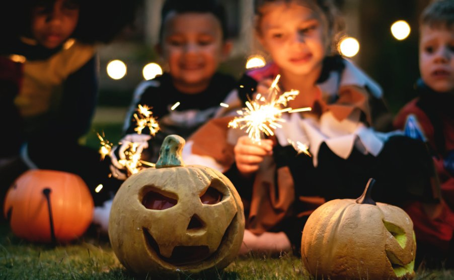 Kids with sparklers and Halloween decor