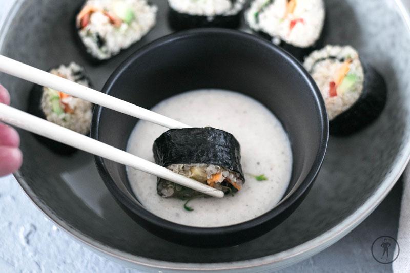 Ein Stück Quinoa Maki wird in Sauce getunkt