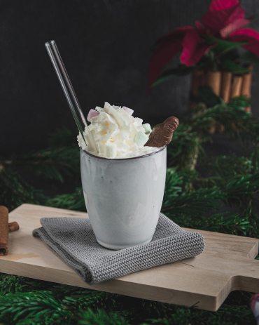Heiße Schokolade mit Schlagobers, Schokodekoration und Glastrinkhalm