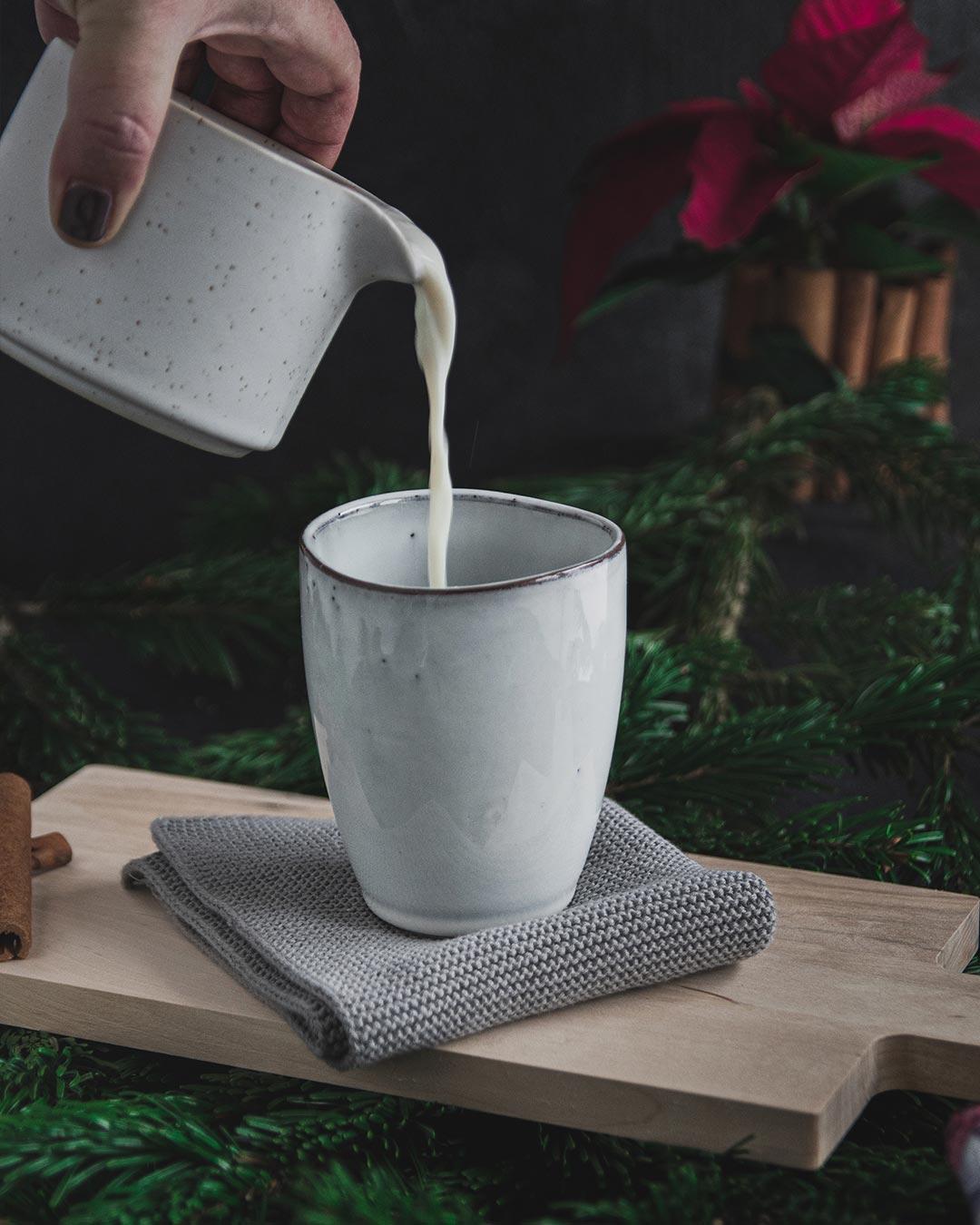 Milch wird aus einem Kännchen in einen Keramikbecher gegossen