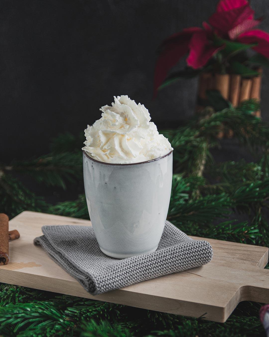 Ein weißer Keramikbecher mit Sahnehäubchen