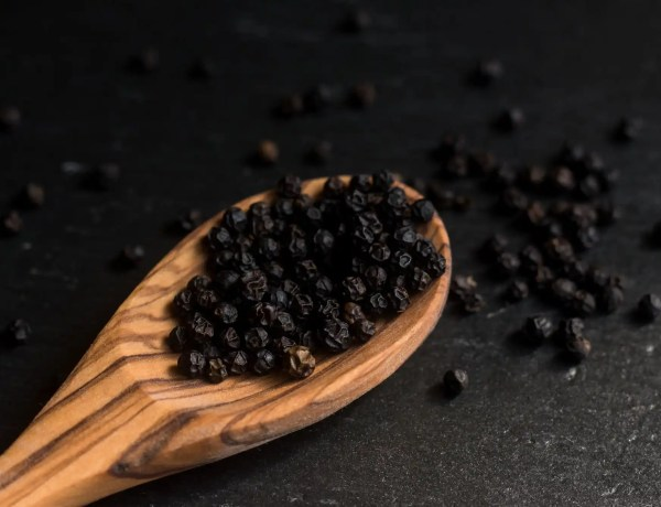 peppercorns in wooden spoon