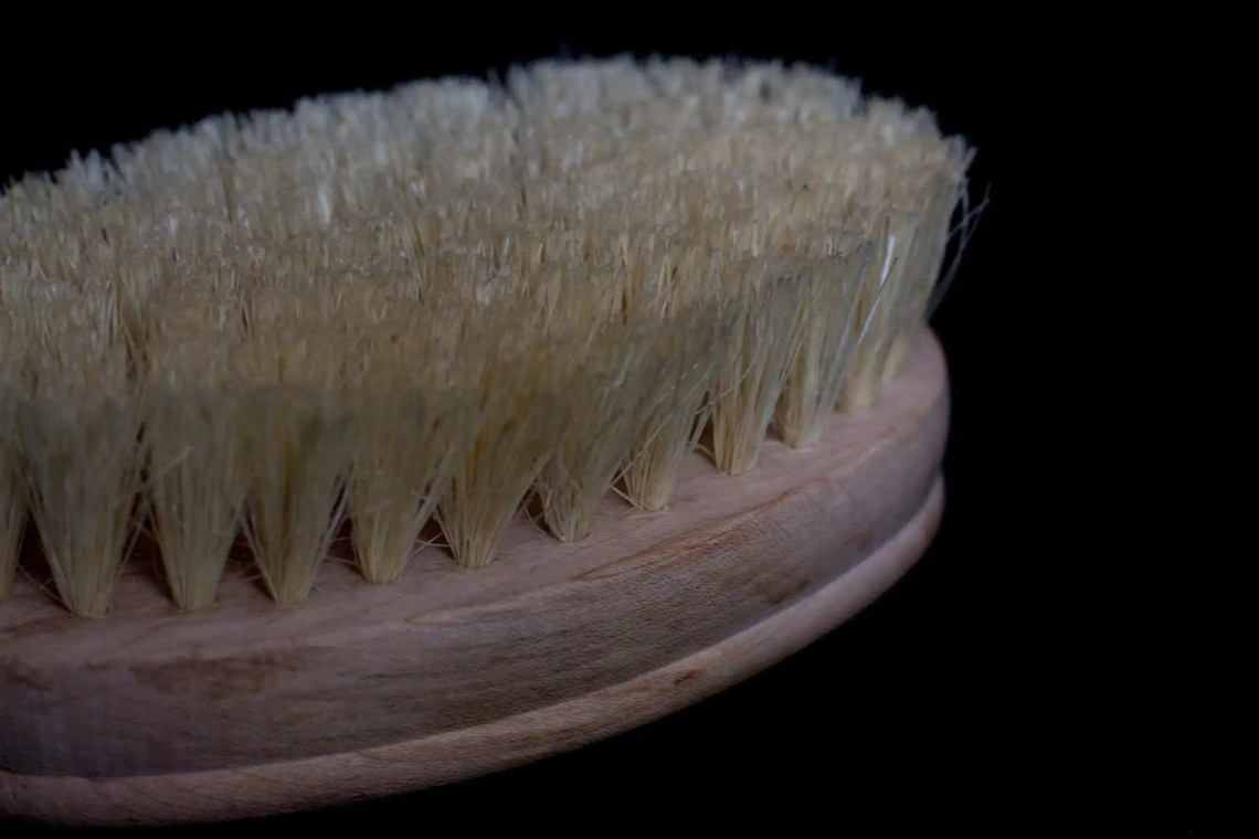 black background with natural fiber dry body brush in foreground for minimalist gift guide
