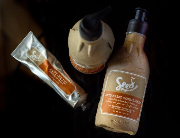 Brown Seed Phytonutrients shampoo and conditioner bottles and aluminum tube of hair cream on black background