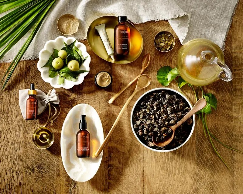 Sahajan Skincare products flat lay with ingredients on wooden background