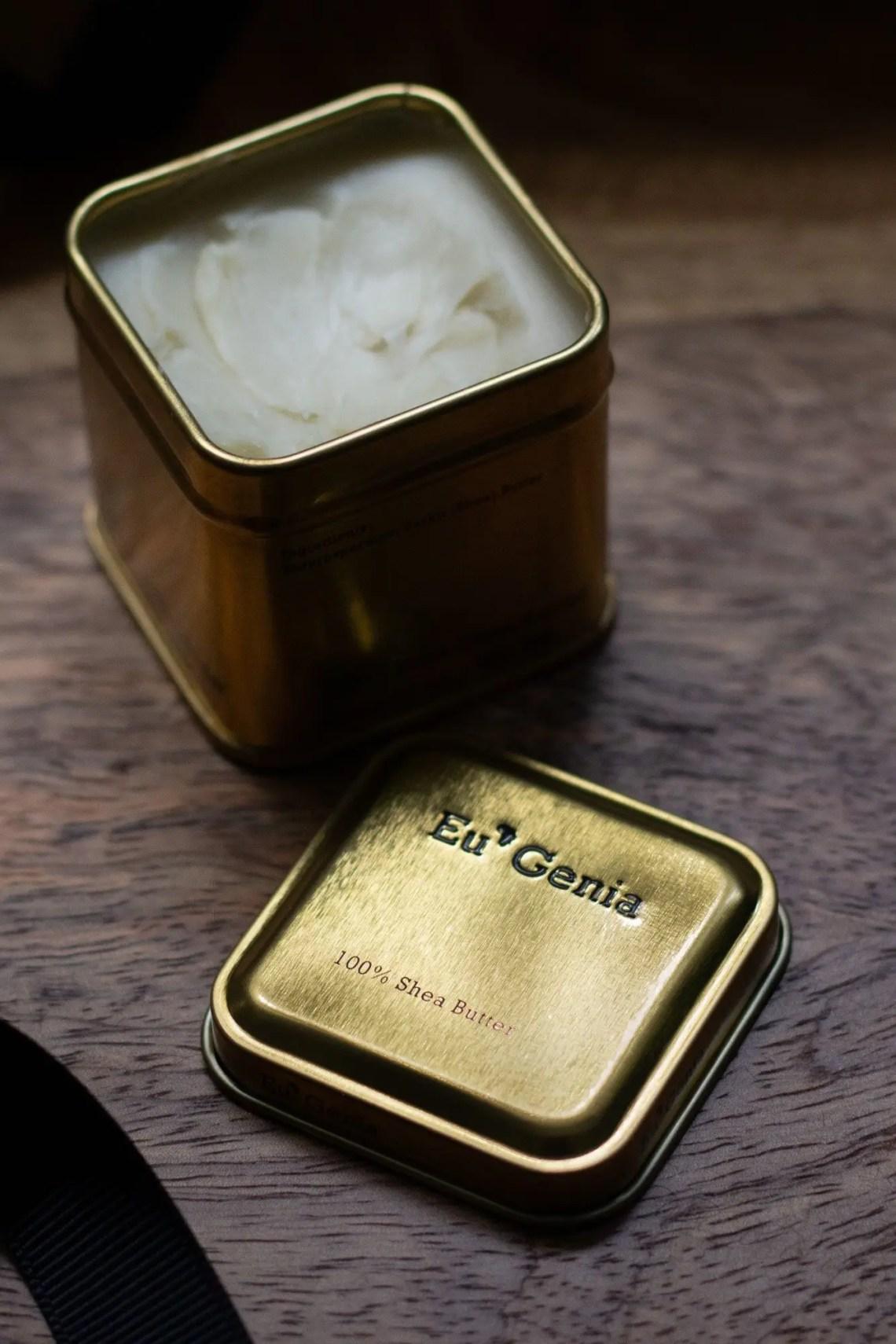 Eu'Genia Shea butter gold tin on wooden dresser