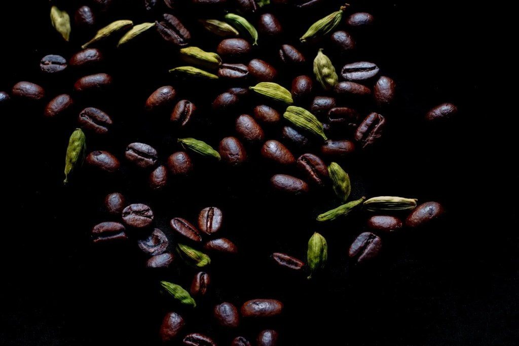 Coffee Beans and Cardamom Pods scattered on black background