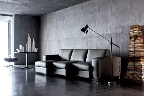 Stile neo dark in soggiorno: pareti nere, divano in pelle nera di Doimo Salotti.