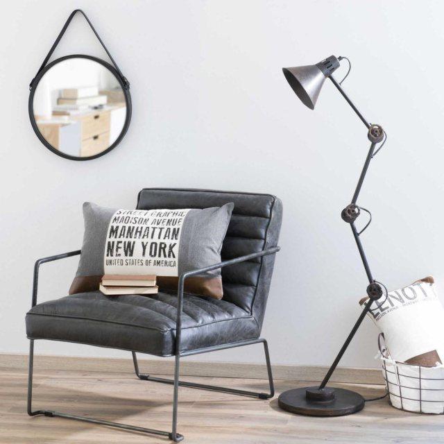 Angolo lettura con poltrona, lampada, specchio e cuscino in stile tropicale.