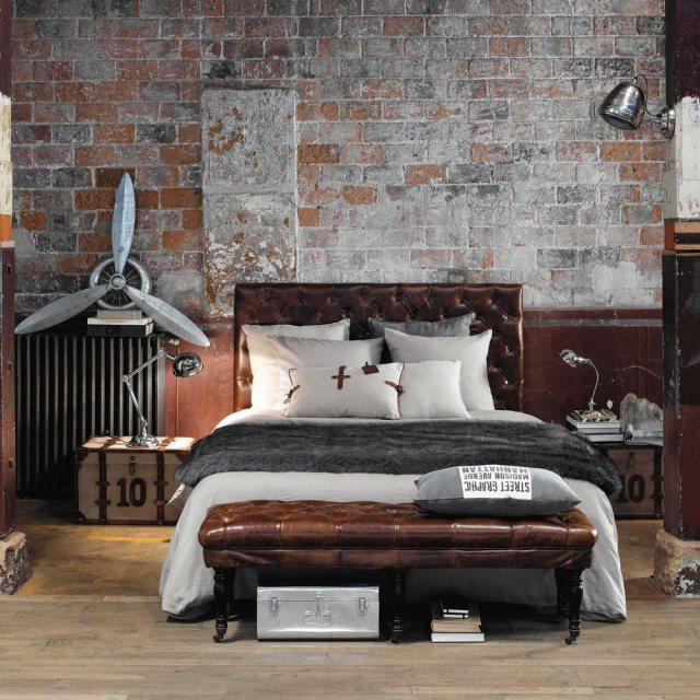 Camera con arredo il stile industriale e cuscini decorativi sopra al letto.