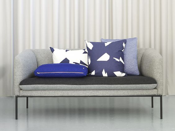 Divano grigio con composizione di cuscini geometrici blu.