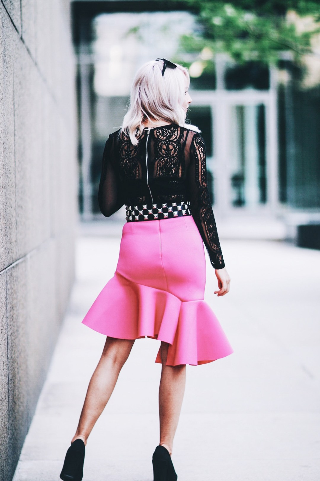 Alena Gidenko of modaprints.com styles a hot pink skirt with a long sleeve lace top, studded belt and black heels