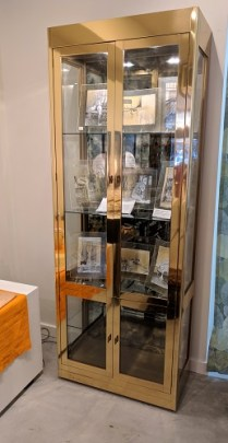 Mastercraft vintage vitrine. Brass and glass. Smoked mirrored glass in behind shelves. Interior lights with dimmer. 1950.-