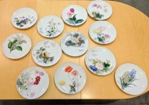 "**ITEM NOW SOLD** Set /12 'Noritake' hand painted plates. Signed: S. Kimura. Discontinued patterns. Drilled for hanging cord. 10.5"" diam. 195.-/set"