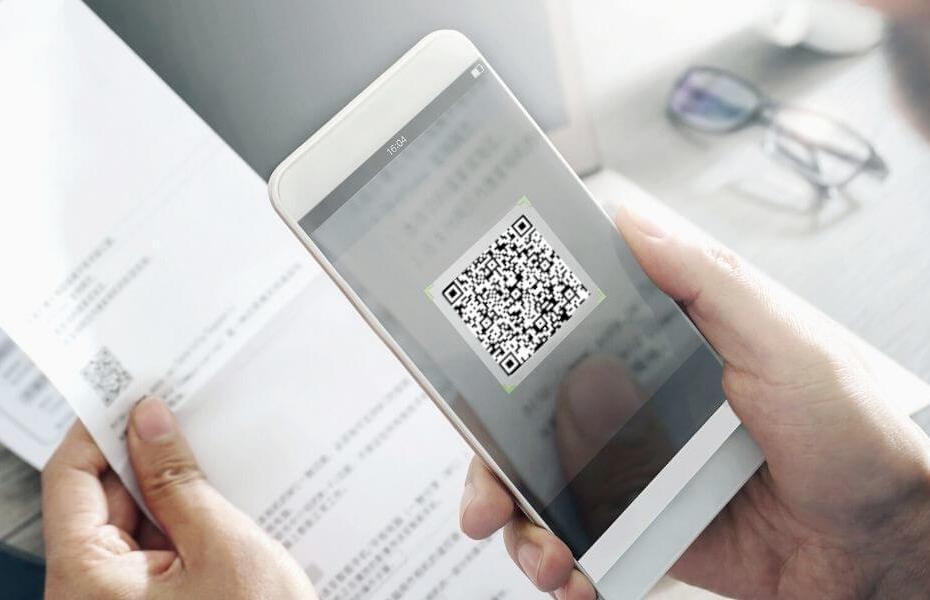 Smartphone scannt QR-Code zur Kontaktnachverfolgung