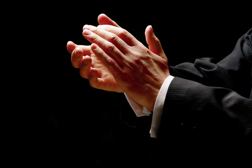 Picture of two hands clapping protruding from a suit with fingers lit