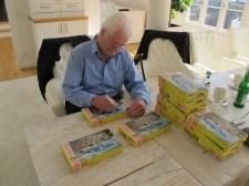 """Der Architekt Leopold Messmer signiert Modelle des von ihm mit-gestalteten Bausatzes """"Villa im Tessin"""" (Bild: Daniel Bartetzko)"""