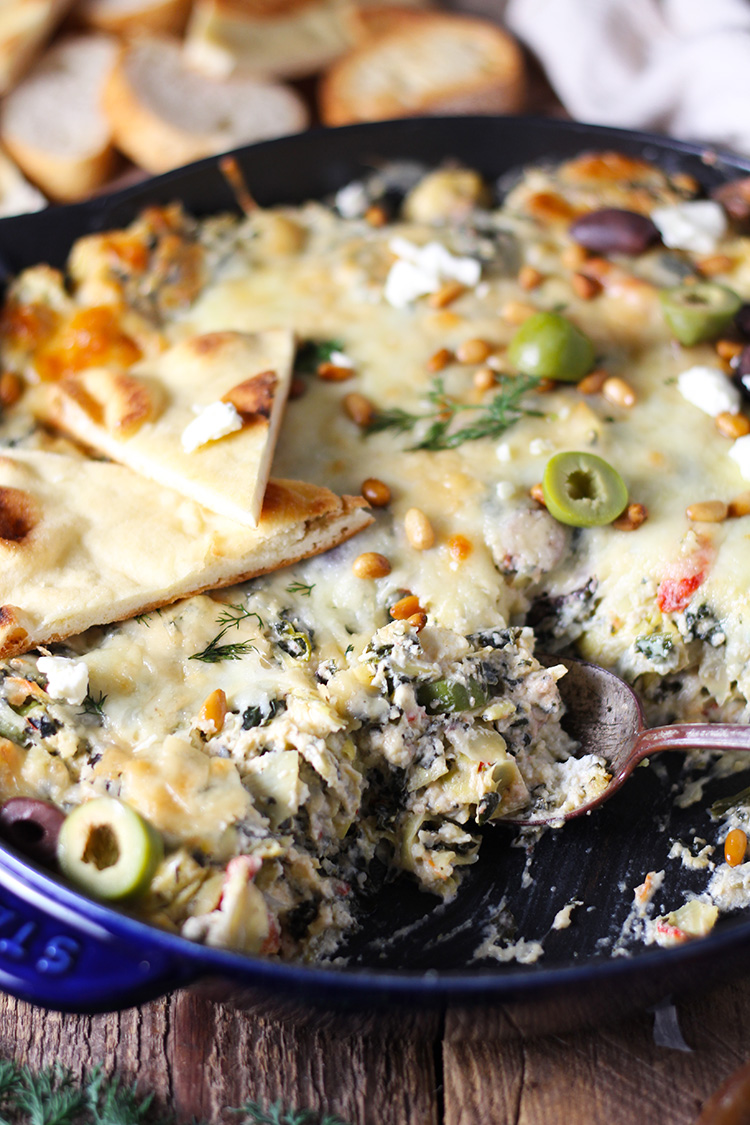 Mediterranean Spinach Artichoke Dip is baked to creamy, cheesy perfection and served with toasted pita bread. Bursting with flavor from spinach, artichokes, olives, and feta cheese, this easy dip is a party favorite!