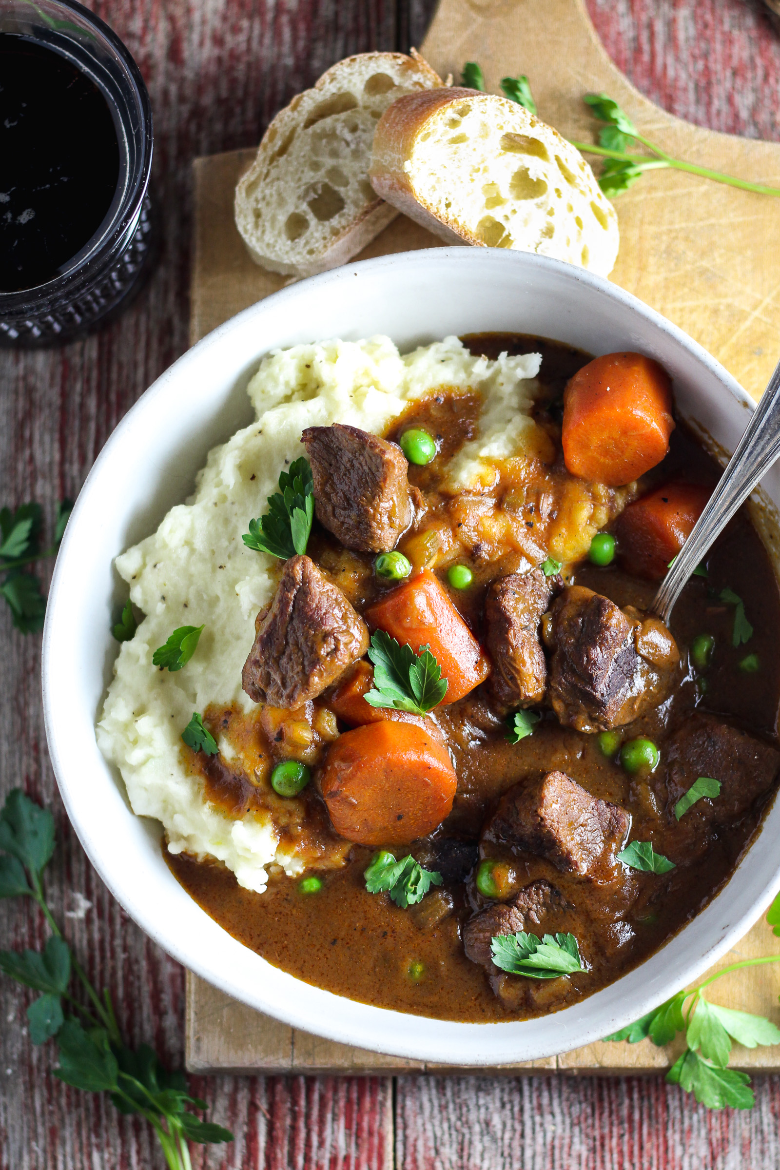 Insanely tender, fall-apart beef, carrots and peas smothered in rich gravy made with Jameson whiskey and Guinness beer. This stew packs incredible flavor and is served over creamy garlic mashed potatoes, making it the ultimate comfort food. Slow cooked in the crockpot, it's easy to make and perfect for feeding a crowd on St. Patrick's Day!