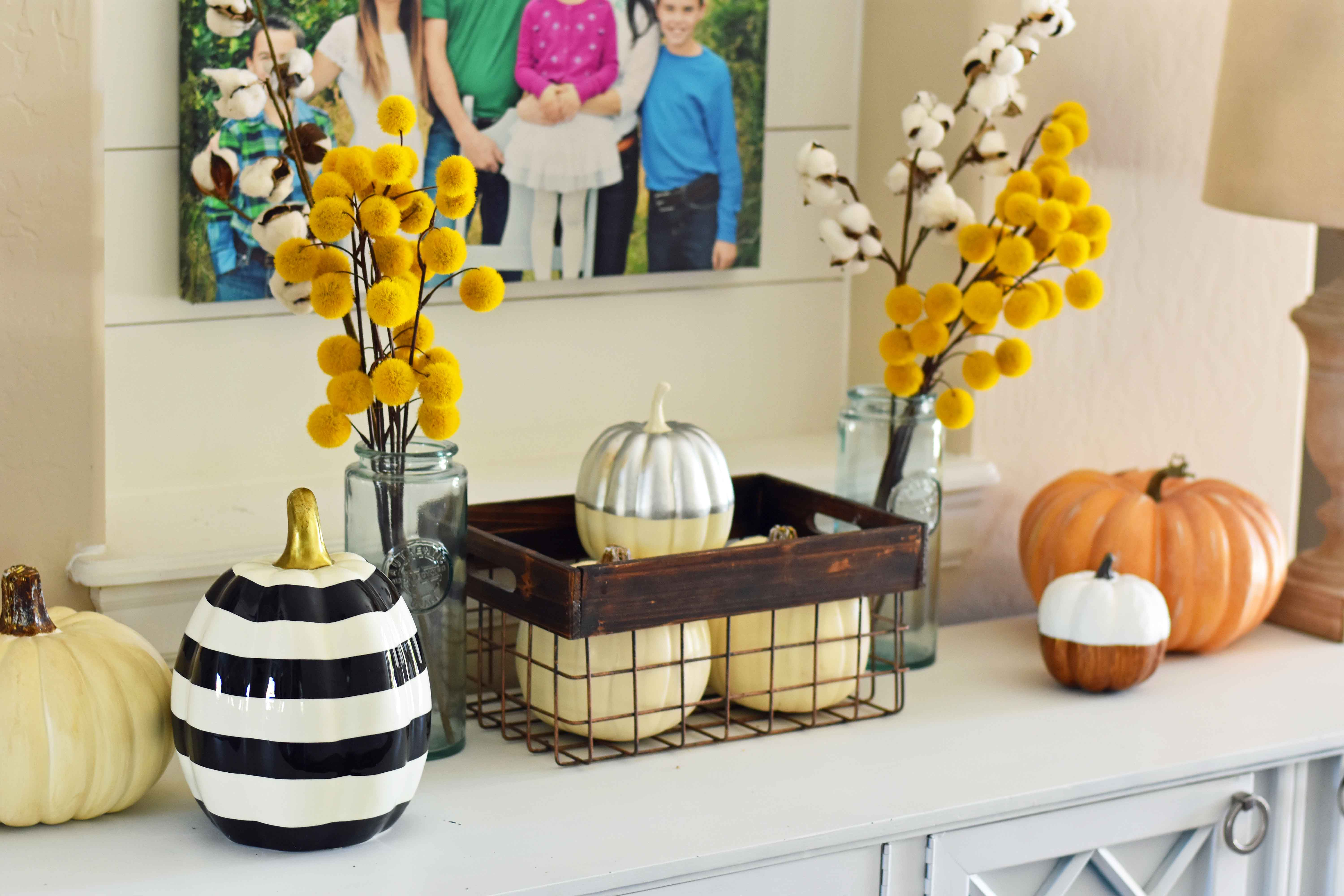 Fall Entry Decor Ideas. Craspedia Yellow Billy Ball Flowers in vintage vases. White pumpkins in wire baskets. Black and white striped pumpkin. Natural lamps, white entry table, and fall decor. Fixer Upper cotton ball stems. How to decorate your home for Fall.