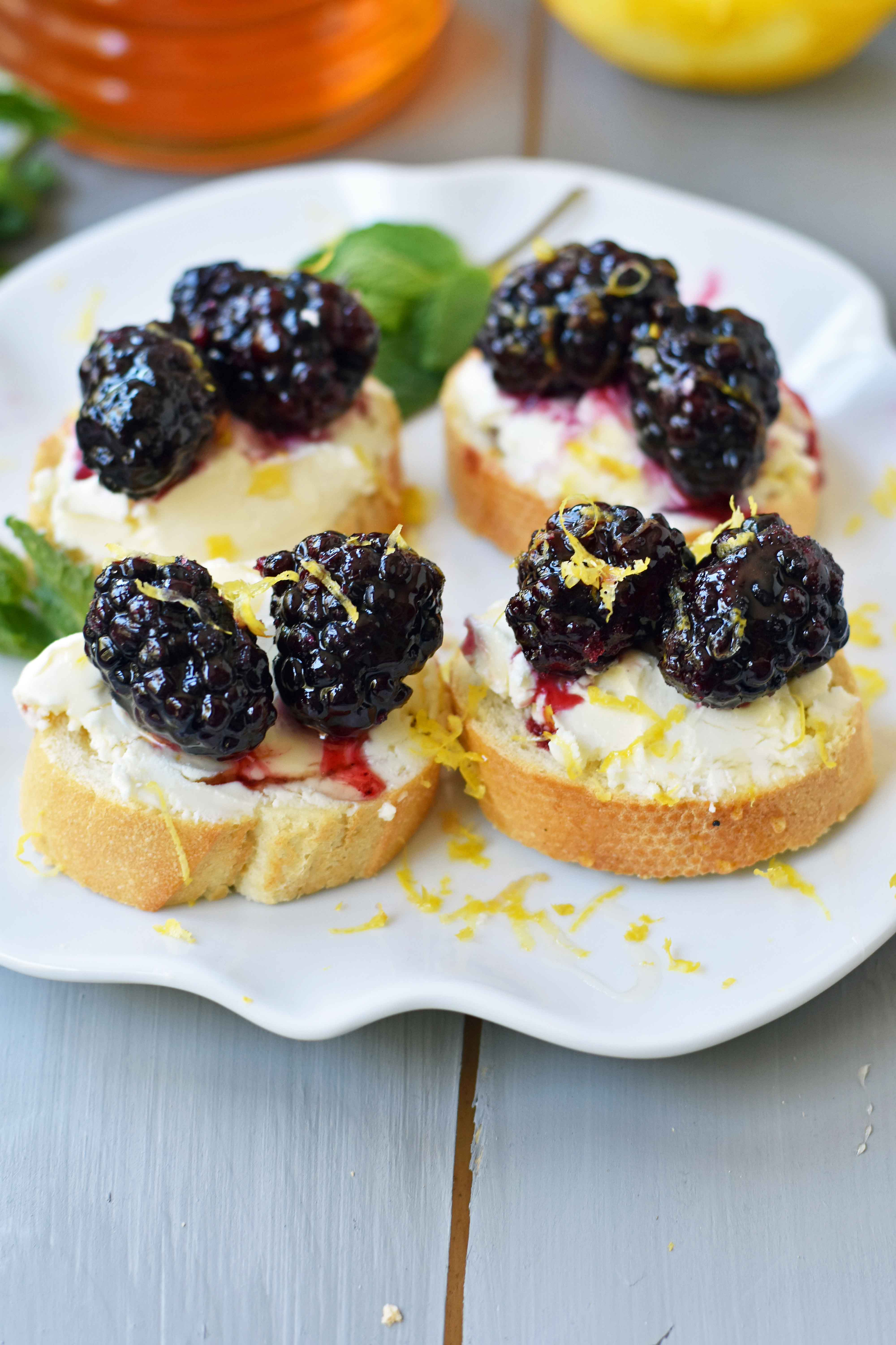 Blackberry and Lemon Mascarpone Crostini. A beautiful appetizer for a bridal shower, baby shower, party, festive holiday party, social gathering or for a dinner at home. A toasted baguette covered in creamy mascarpone cheese and topped with sugar marinated blackberries, fresh lemon zest, and a drizzle of honey. A sophisticated yet delicious appetizer. www.modernhoney.com