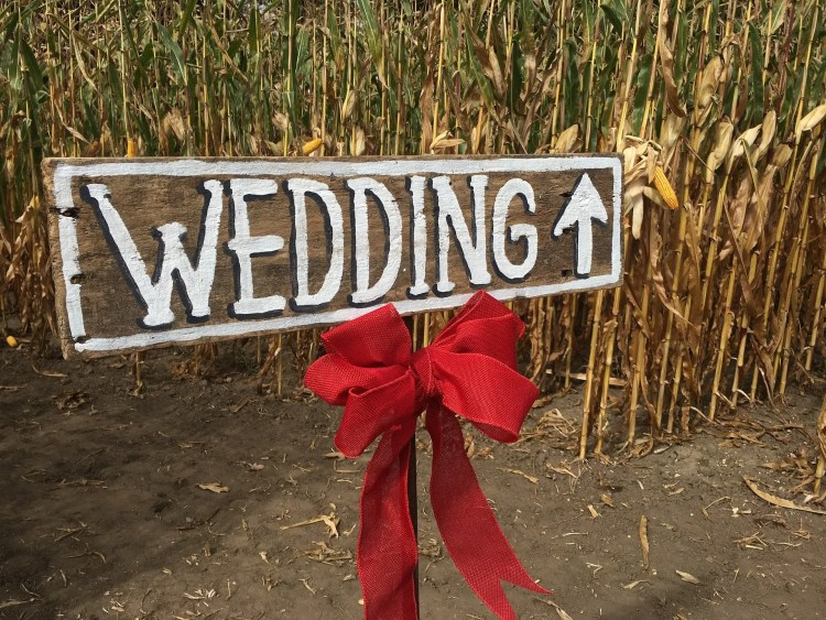 Rustic wedding decorations idea - wedding sign on wood with white writing and a red bow