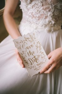 Woman holding a save the date card - example of rustic wedding invitations