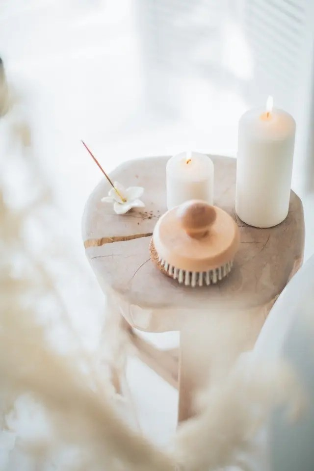 Image depicts a circular tray with incense, a candle and body brush on it.