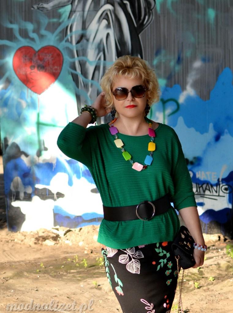 Czarna ołówkowa spódnica i zielona bluzka na tle murali