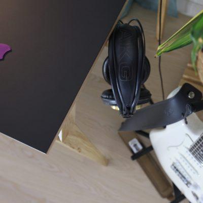 Pogled na slušalice koje vise sa bočne kukice radnog stola Conform Deska