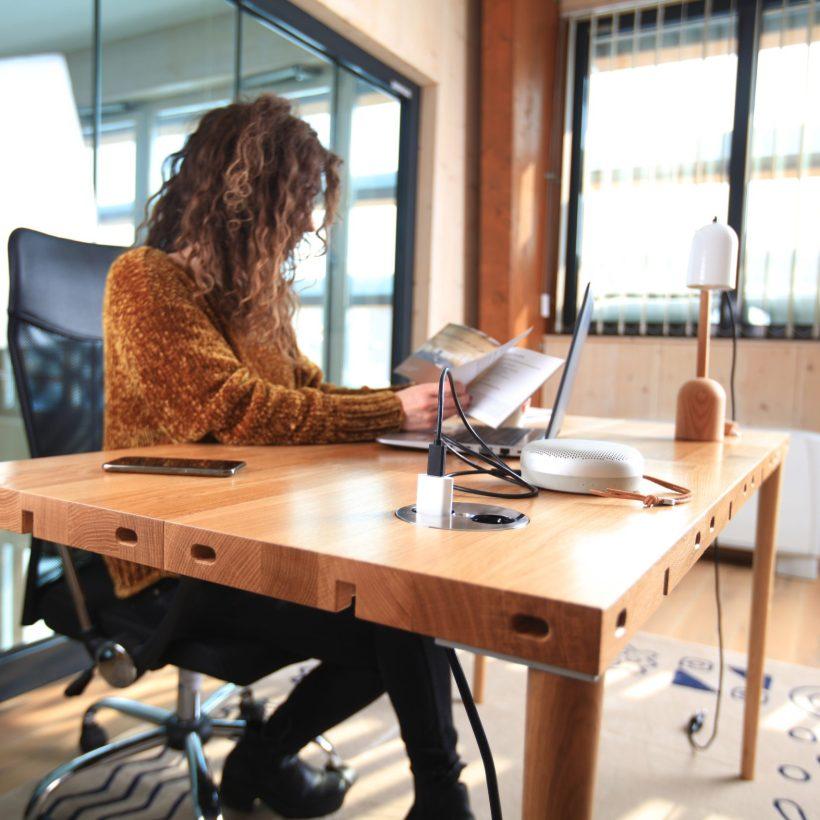 Djevojka sjedi za modularnim radnim stolom Modulos koji je napravljen od hrasta